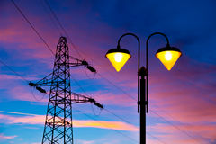 Electricity pylon and streetlamp at sunset Royalty Free Stock Photography