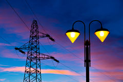 Electricity pylon and streetlamp at sunset Stock Photo