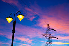 Electricity pylon and streetlamp at sunset Royalty Free Stock Image