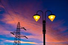 Electricity pylon and streetlamp at sunset. Lit on streetlamp at sunset with high-tension line and pylon on the background Stock Photography