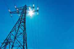Electricity pylon with sun and sky Stock Photo