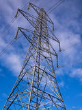 Electricity Pylon Tower. Suspension tower electricity pylon seen from below, against a blue sky with white clouds stock photography