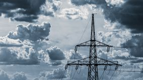 Electricity pylon top on a cloudy sky background. Close-up of the power tower with wires of electric transmission system. Dramatic blue cloudscape, dark ominous royalty free stock image