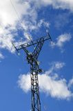 Electricity pylon and white clouds. High voltage tower against blue sky and white clouds royalty free stock photography