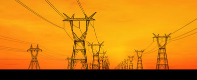 Electricity pylons. Silhouetted electricity pylons receding into distance with orange sunset background Stock Photography