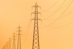 Electricity pylons. Pylons supporting overhead electricity conductors at the sunset Stock Images