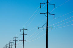 Electricity pylons. Electricity power distribution pylons with sun reflecting on wires Royalty Free Stock Image