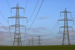 Electricity Pylons. Photo of electricity pylons and cables leading into the distance Stock Photos