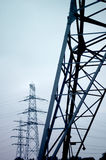 Electricity Pylons. Three electricity pylons with blue background Stock Photo