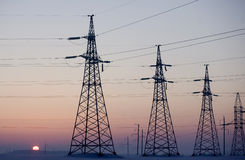 Electricity pylons. And lines above a freeway  at sunrise Royalty Free Stock Images