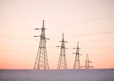 Electricity pylons. And lines above a freeway  at sunrise Stock Photos