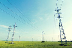Electricity pylons. And wires in a green field against blue sky stock photos