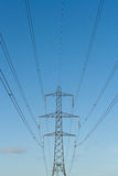Electricity pylons. Array of electricity pylons against sea-ice blue sky Royalty Free Stock Image