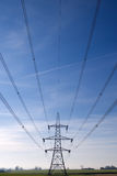 Electricity Pylons. Electricity pylon and cables stretching out into the distance across a green field stock photos