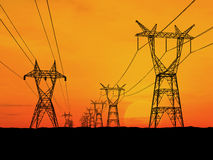 Electricity pylons. At orange sunset Royalty Free Stock Photos