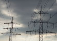 Electricity pylons against dark clouds. Behind electricity pylons appear dark clouds Stock Photo