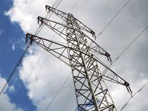 Electricity pylons against white clouds. Behind a power pole a white cloud appears in the sky Royalty Free Stock Photo