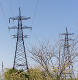Electricity pylons bearing the power supply across a rural landscape. Stock Images