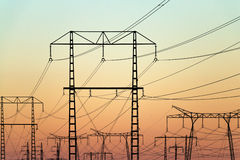 Electricity pylons on colorful evening sky Stock Photos