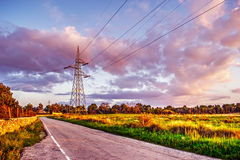 Electricity pylons by a country road Royalty Free Stock Photography