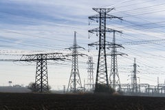 Electricity pylons with distribution power station blue cloudy sky background Royalty Free Stock Photo