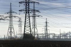 Electricity pylons with distribution power station blue cloudy sky background Stock Photo