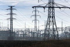 Electricity pylons with distribution power station blue cloudy sky background Stock Photography