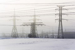 Electricity pylons from distribution power station in foggy winter freeze. Weather Stock Photography