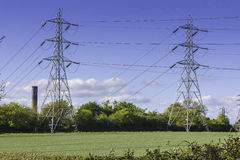 Electricity Pylons in Field. A view of a pair of Electricity Pylons in a field with blue sky Stock Image