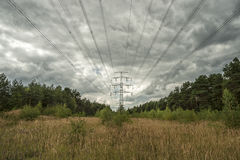Electricity Pylons in fields with cloudy sky Stock Photography