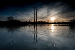 Electricity pylons in flooded field Royalty Free Stock Image