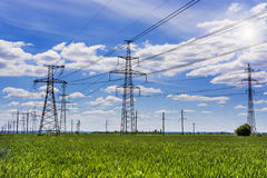 Electricity pylons going into the distance over summertime countryside. Stock Images