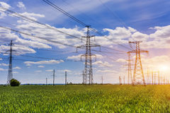 Electricity pylons going into the distance over summertime countryside. Royalty Free Stock Photo