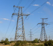 Electricity pylons going into the distance over summertime countryside. Stock Photo