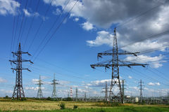 Electricity pylons in the green field Royalty Free Stock Images