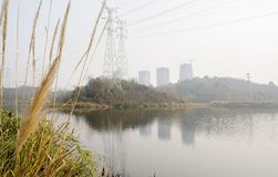 Electricity pylons on hill near modern city in sunny winter afternoon. Electricity pylons on the hill near modern city in sunny winter afternoon,Chengdu,China stock images