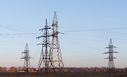 Electricity pylons and lines at dusk. Royalty Free Stock Photo