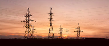 Electricity pylons and lines at dusk. Royalty Free Stock Photography