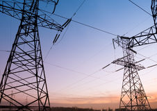 Electricity pylons and lines at dusk. Stock Image