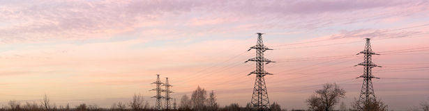 Electricity pylons and lines at dusk. Panorama. royalty free stock image
