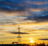 Electricity pylons and lines at dusk at sunset. Royalty Free Stock Images