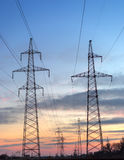 Electricity pylons and lines at dusk at sunset. Royalty Free Stock Photos