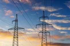 Electricity pylons and lines at dusk at sunset. Stock Images