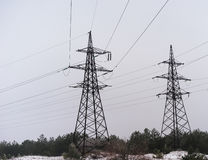 Electricity pylons and lines at dusk at sunset. Royalty Free Stock Photography