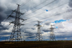 Electricity pylons and lines at dusk at sunset. Stock Photography