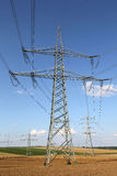 Electricity pylons and lines on a field Stock Photography