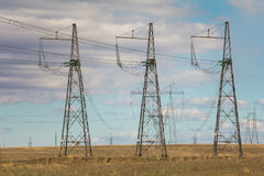 Electricity pylons and lines at summer field, sunny day stock photo