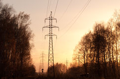 Electricity pylons and lines at sunset. Royalty Free Stock Images