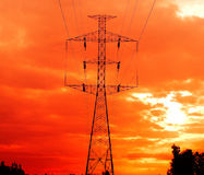 Electricity pylons  in orange sky. Stock Images