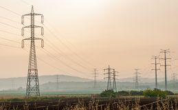 Electricity pylons over an arable land Stock Images